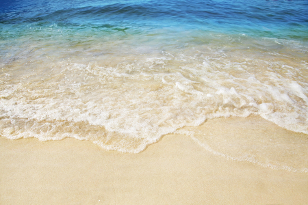 Spiaggia sabbiosa. Spruzzi di onde in riva al mare. Estate.