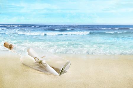 Una botella con una letra adentro. Playa de arena. Foto de archivo