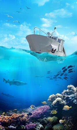 Small fishing boat in the ocean. Underwater view of the coral reef. Shoal of fish.