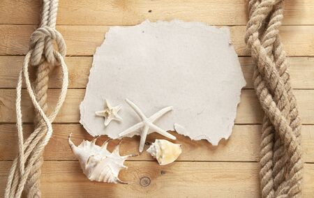 Old sheet of paper on board the ship. Shells and starfish. Wooden background. Zdjęcie Seryjne