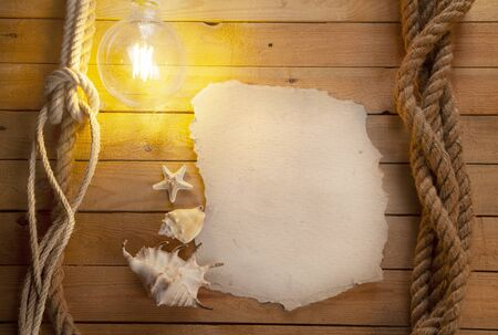 An old piece of paper lit by a light bulb. Wooden background. Shells and starfish. Space for text. Deck of an old ship.