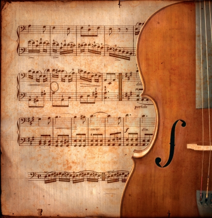 violins: cello on ancient music sheet, rusted old yellow paper with guitar