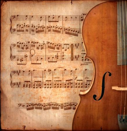 chiave di violino: cello sul foglio antico di musica, vecchia carta gialla arrugginita con il guitar