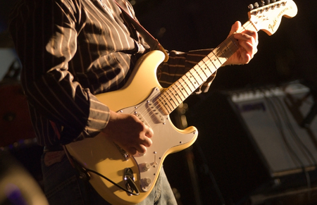 man playing electrical guitar during concert