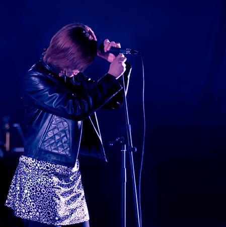 shure: girl singing in concert on dark background blue Stock Photo