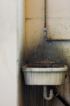 dirt and desgusting washbasin with pipes in a old industry