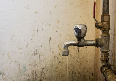 old and dirty faucet with pipes and water  photo