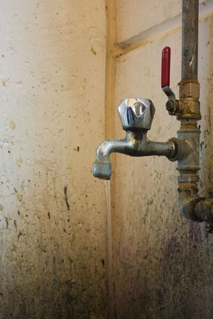 dilapidated wall: old and dirty faucet with pipes and water