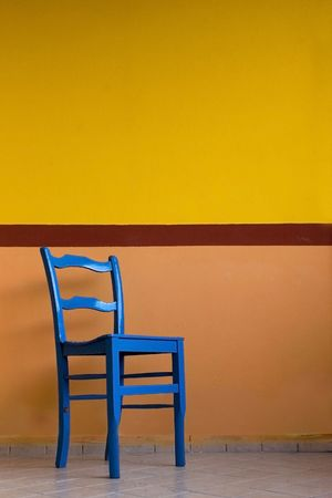 unoccupied: Blue chair against a yellow painted wall, in italy