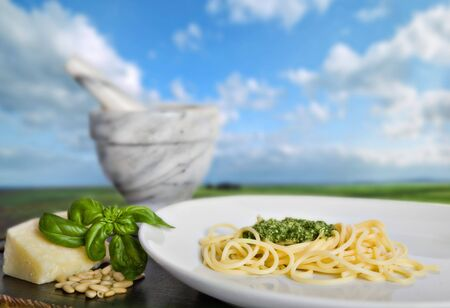 european cuisine: Spaghetti al pesto (a tipical italian basils sauce), in front of a beautiful italian landscape