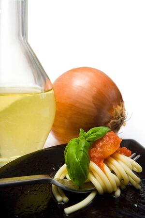 european cuisine: spaghetti with fresh tomato and basil, with onion and olive oil in background Stock Photo