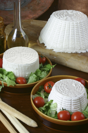 brea: selection of italian fresh cheese and ricotta on wood background
