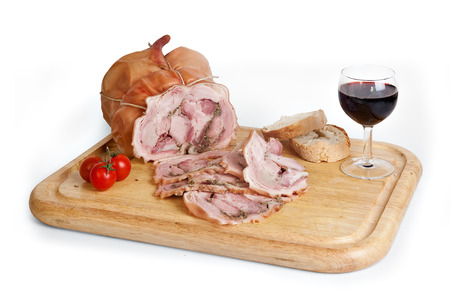 Pork roast on wooden cupboard with wine and tomatoes