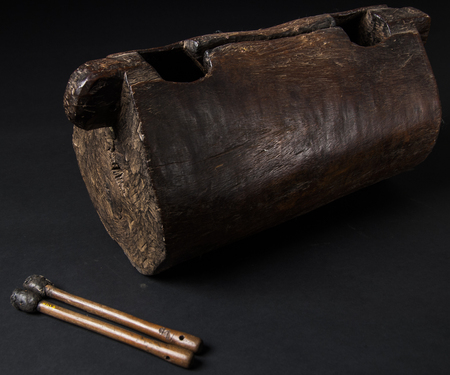 instrument of African music, drum made of wood with two bakets, isolated on dark background