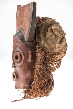 fearful: African wooden mask with hair, isolated on white background Stock Photo