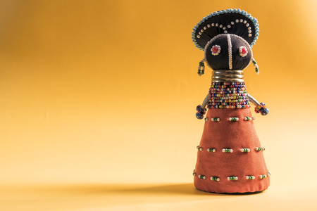 African cloth doll isolated on yellow background