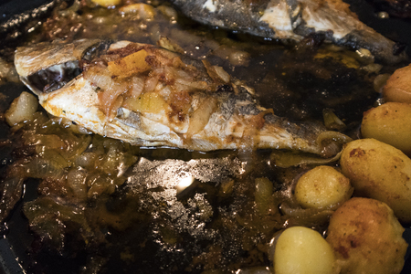 oven potatoes: Fish baked in the oven, golden with boiled potatoes and olives in white dish. Typical Portuguese dish.