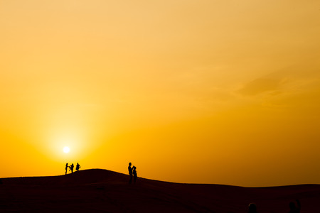 Silhouette of people in dubai desert, with sunset.
