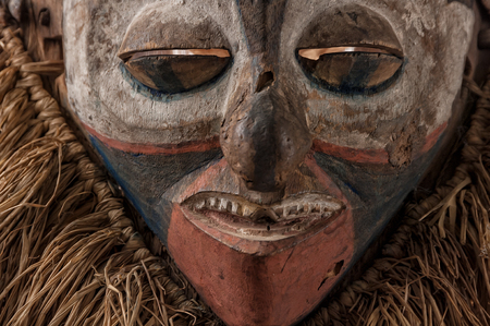 Hand made African mask with ropes simulating hair. Human face. Isolated on white background.close up