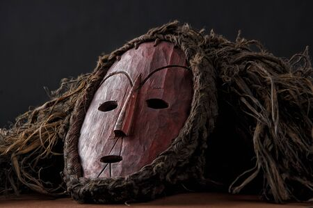 African wooden mask, with hair isolated on black background.