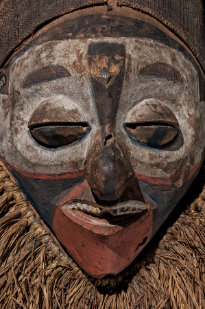 Hand made African mask with ropes simulating hair. Human face. Isolated on black background. close up