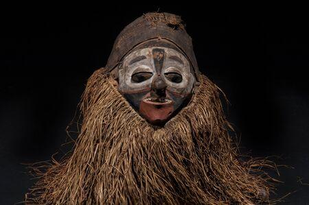 Fait à la main masque africain avec des cordes simulant les hommes. visage humain isolé. isolé sur fond noir Banque d'images - 82163292