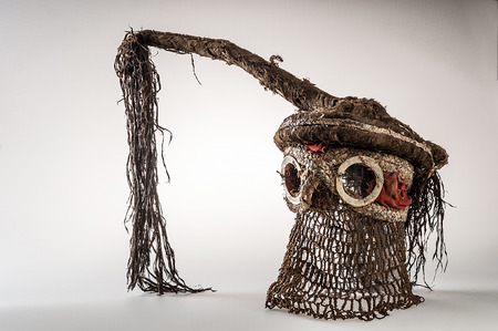 Hand made African mask with ropes simulating hair. isolated on white background