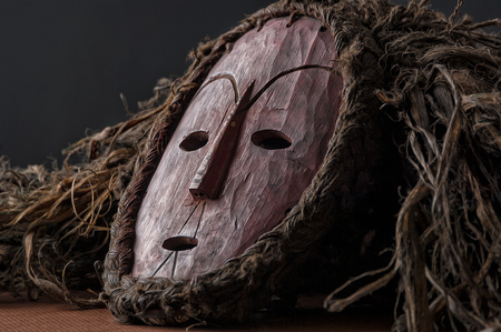 African wooden mask, with hair isolated on black background. close up.