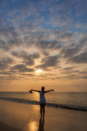 Silhouette of young girl with open arms, with sunset and dramatic sky.