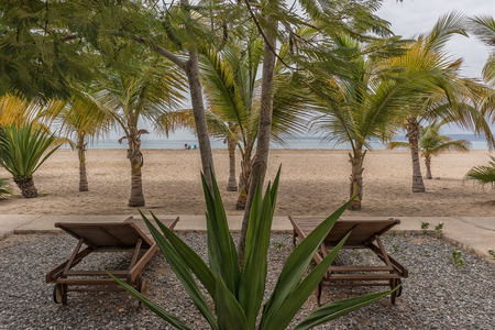 Wooden chairs on tropical beach, Cabo Ledo, Angola