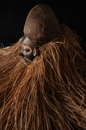 Hand made African mask with ropes simulating hair. Human face. Isolated on black background.