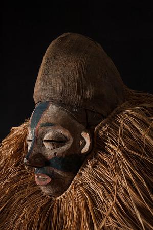 Masque africain fait à la main avec des cordes simulant les cheveux. Visage humain. Isolé sur fond noir. Banque d'images - 83718237