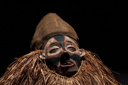 Masque africain fait à la main avec des cordes simulant les cheveux. Visage humain. Isolé sur fond noir. Banque d'images - 83718242