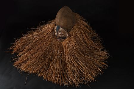 Masque africain fait à la main avec des cordes simulant les cheveux. Visage humain. Isolé sur fond noir. Banque d'images - 83718197