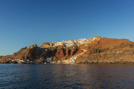 view of Oia, Greece Santorini, view from the sea with sunset.