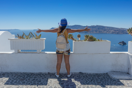 Young girl with wide open arms overlooking the caldera. Oia, Santorini. Greece. Stock Photo