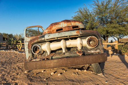 Old and abandoned car in the desert of Namibia. Solitaire. With the beautiful light of the sunrise. Stock Photo