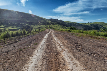 Mud road with tire marks runs through green valley in Malanje. Angola. Africa. 스톡 콘텐츠