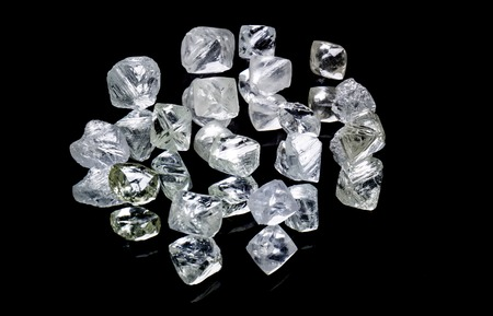 Raw diamonds isolated on black background.