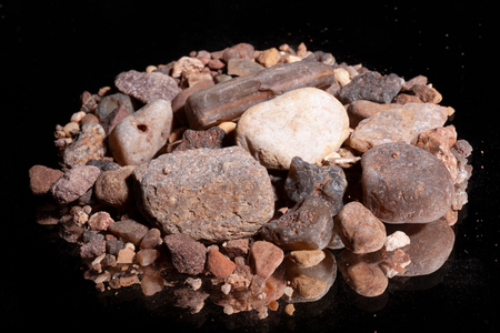 Ore from a diamond mine. isolated on black background with reflexion.