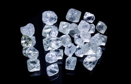 Raw diamonds isolated on black background.