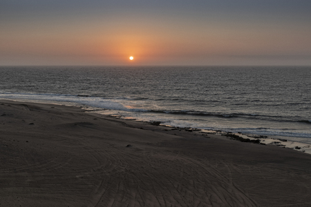 Beautiful sunset on the wild Namibe beach with canyons and desert.