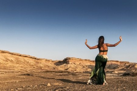 Active woman dancing on plain of the Namibe Desert. Africa. Angola.