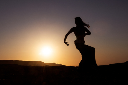 Silhouette of Woman dancing to the famous belly dance with sunset in the Namibe Desert with canyons. Africa. Angola. Stock Photo