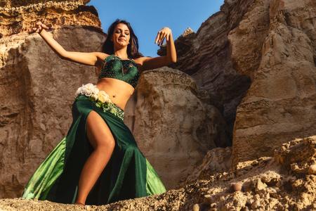 Junges Mädchen im grünen Kleid, das den berühmten Bauchtanz tanzt, im mythischen Raum der Schluchten der Namibe-Wüste. Afrika. Angola.