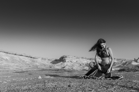 Woman dancing to the famous belly dance with natural sunset light, in the Namib Desert with canyons. Africa. Angola. Bw version.