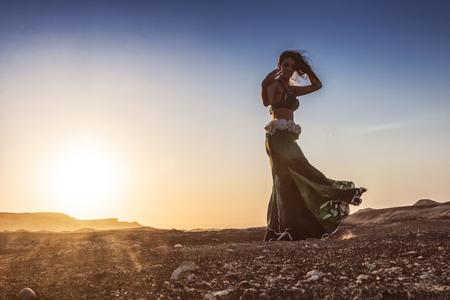 Femme dansant sur la célèbre danse du ventre avec coucher de soleil, dans le désert du Namib avec des canyons. Afrique. Angola. Banque d'images