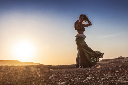 Woman dancing to the famous belly dance with sunset, in the Namib Desert with canyons. Africa. Angola. Reklamní fotografie
