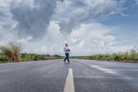 SOYO/ANGOLA - 20 JAN 2019 - Photographer to cross tar road in Soyo, Africa. With camera in hand. Angola