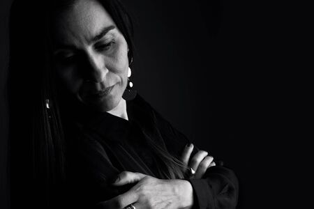 Portrait of middle-aged woman with black background. Bw version
